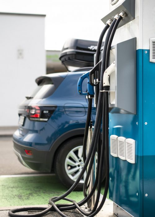 Electric car on gas station. Blue car and electric plug for char